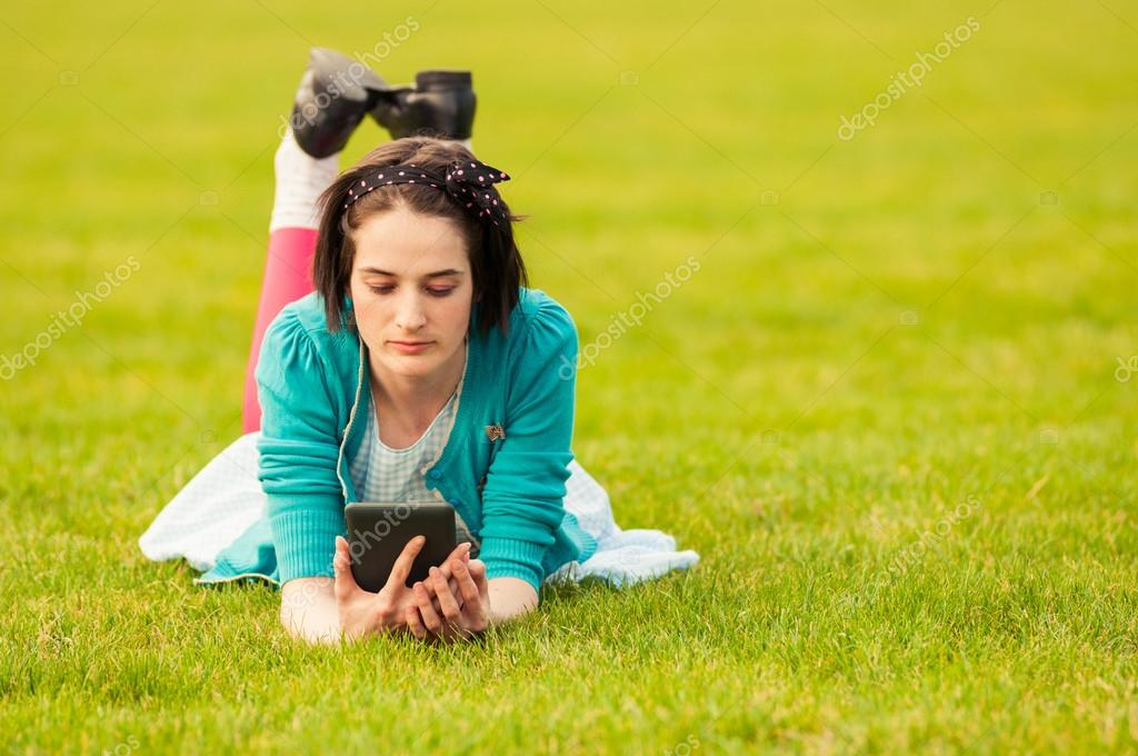 Attractive female using tablet outdoor while sitting on grass