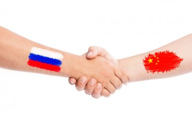 Russia and China hands shaking with flags