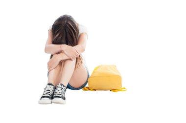 Upset girl holding head on knees