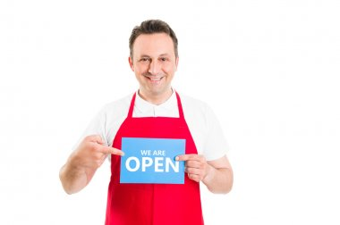 Friendly supermarket employee holding open sign