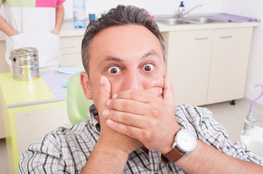 Scared man at dentist covering his mouth