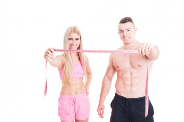 Healthy fitness couple holding meter or centimeter