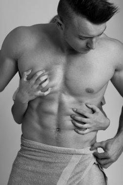Passion concept with woman hand touching muscular man chest