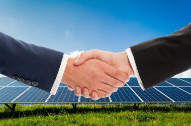 Businessmen handshake on solarpower photovoltaic panel backgroun