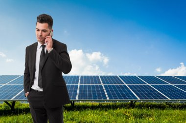 Businessman talking on the phone on solar power panels backgroun