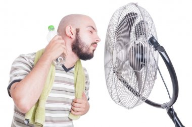 Man cooling his neck with cold water bottle and fan