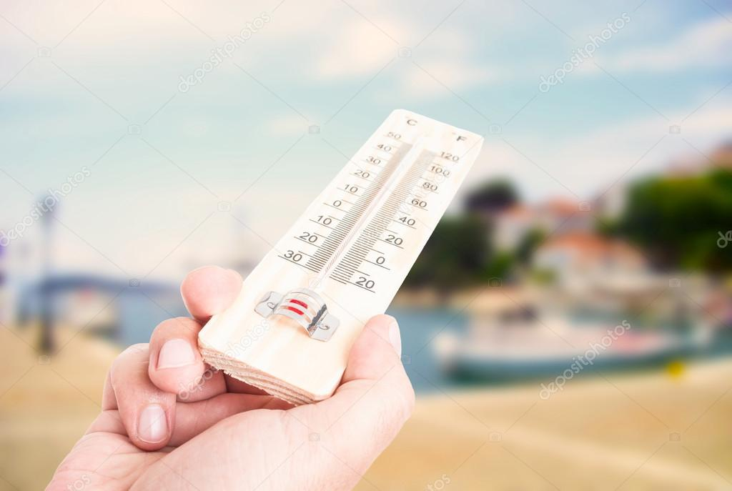 Hand holding thermometer on city with lake background