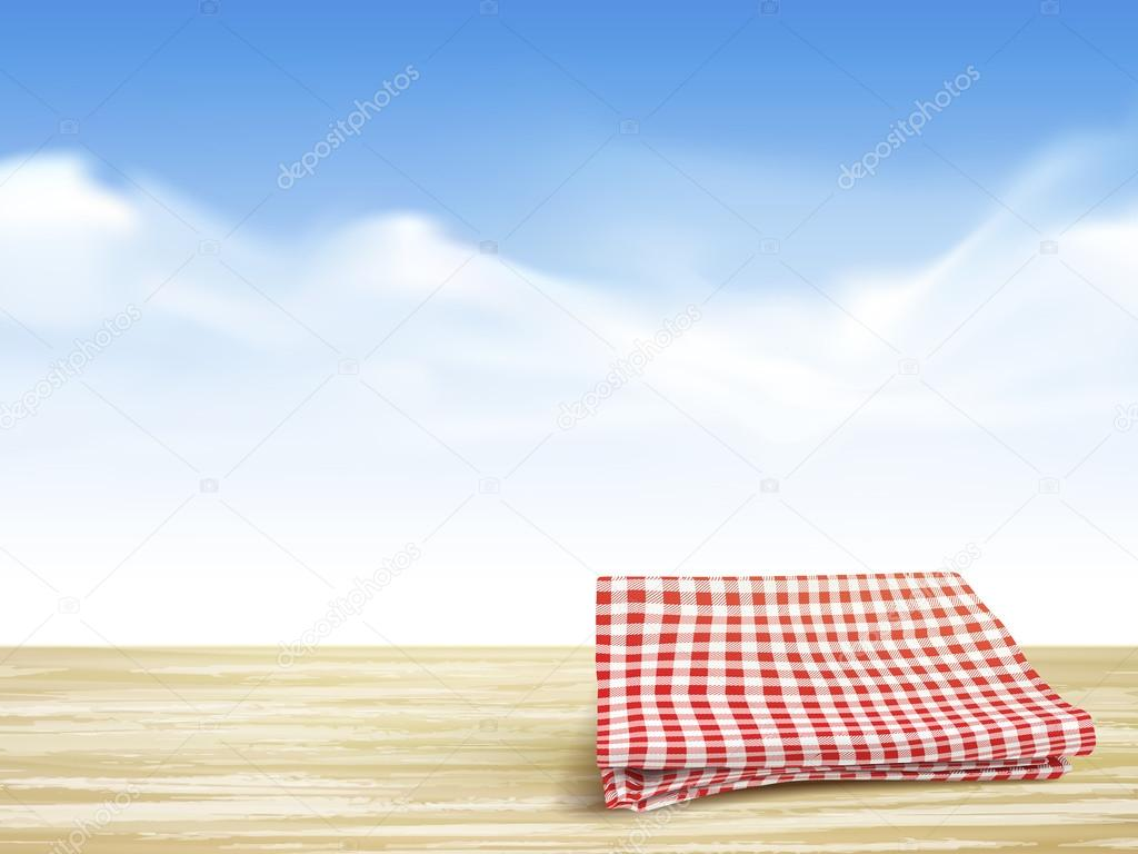 closeup of wooden desk and tablecloth over blue sky