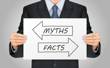 businessman holding myths or facts poster