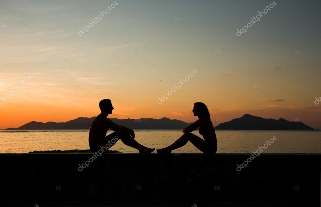 Silueta. Mujer Y Hombre Joven Sentarse Juntos Al Atardecer