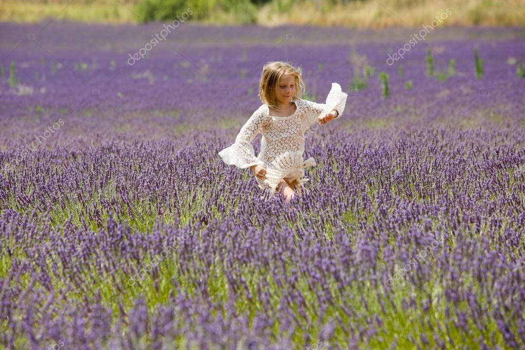 Beautiful blonde girl runs through a lavender field