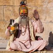 hindu sadhu heiliger Mann, sitzt auf dem Ghatt, sucht Almosen auf der Straße in Jaisalmer, Rajasthan, Indien