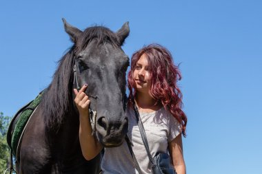 Beautiful girl and black horse in nature. Kiev, Ukraine
