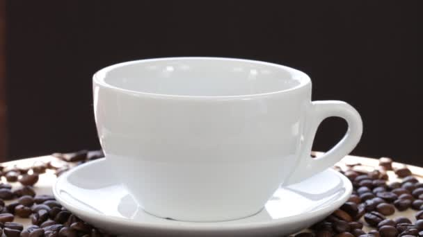 White cup with a black tea. Coffee or Tea. Cup of hot beverage with steam in black background