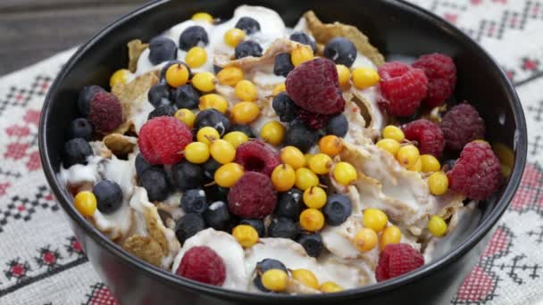 Cereal flakes with blueberries, raspberries and sea buckthorn pour yogurt . Crunchy tasty muesli food background close up
