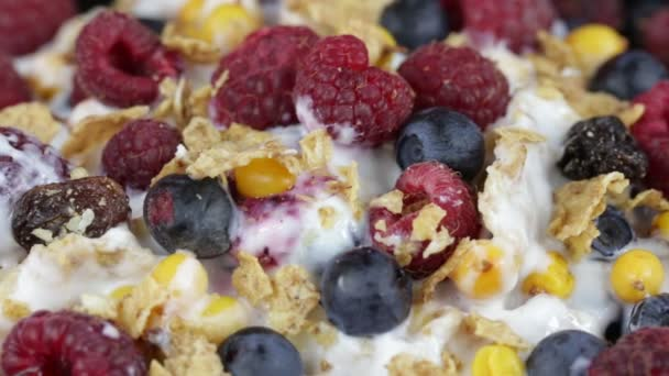 Cereal flakes with blueberries, raspberries and sea buckthorn rotating . Crunchy tasty muesli food background close up