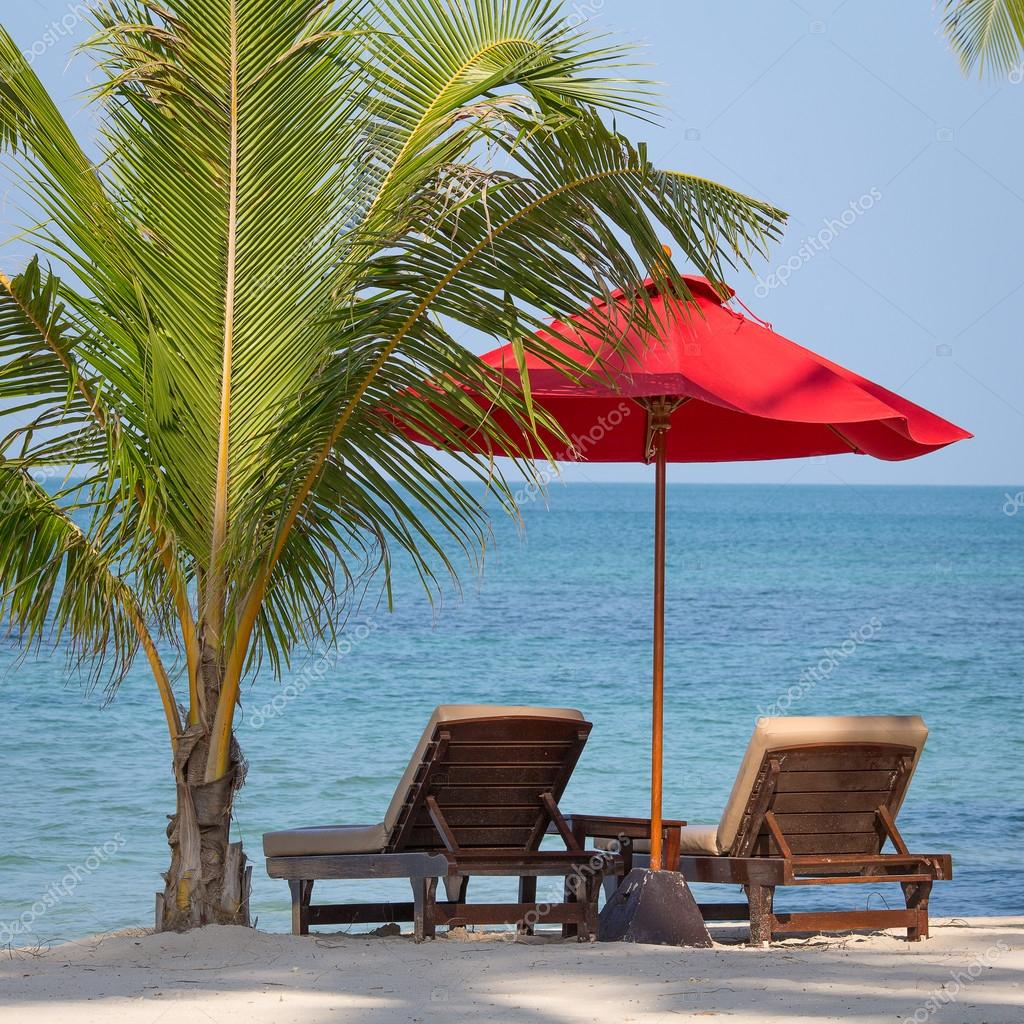 Two beach chairs, red umbrella and palm tree on the beach in Thailand
