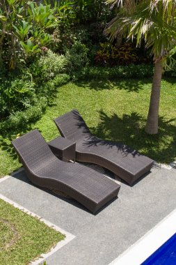 Couple of sun loungers beside the pool in tropical garden.  Bali, Indonesia