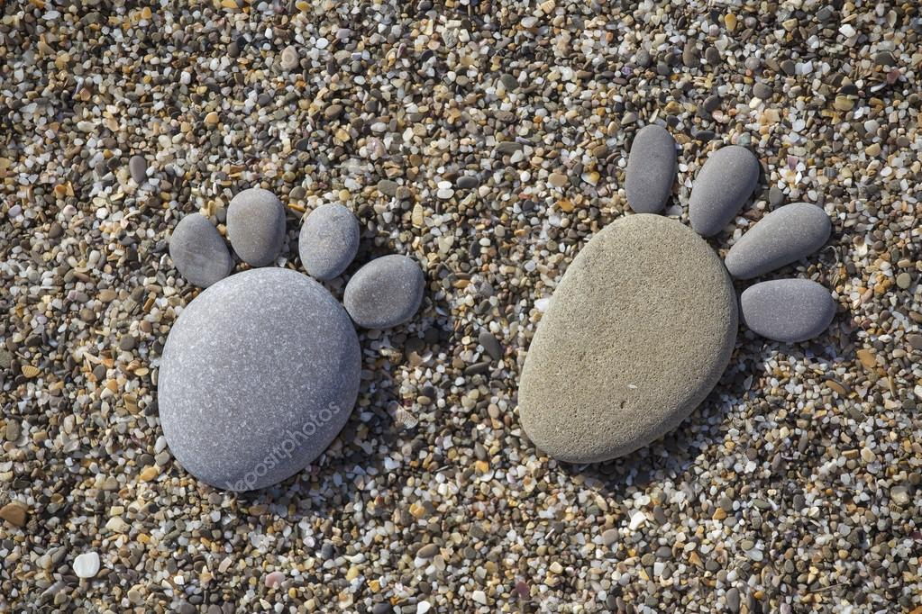 Two trace feet made of a pebble stone on the beach backdrop