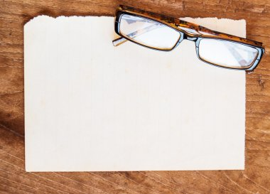 old paper and glasses on wood background
