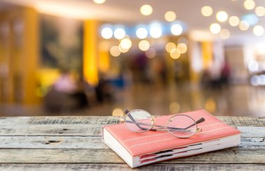 Notebook and eyeglasses on wooden table with blurred hotel lobby
