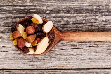Mixed nuts on a wooden spoon.
