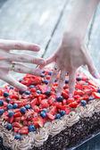 Fotografie paar Hände mit Ehering und Schokoladenkuchen mit Beeren