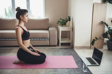 Caucasian woman sitting on the floor in front of a laptop and glass with water in sportswear getting ready for online fitness lesson