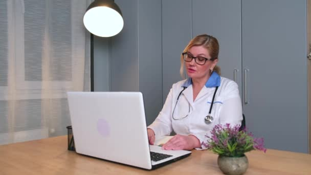 Senior blonde doctor is speaking with a patient online in a video call using a laptop at the office