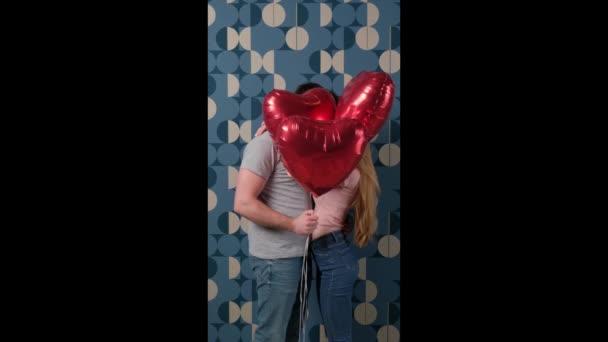 Rozkošný pár líbání za červenými balónky na modré zdi, zatímco mají spolu rande