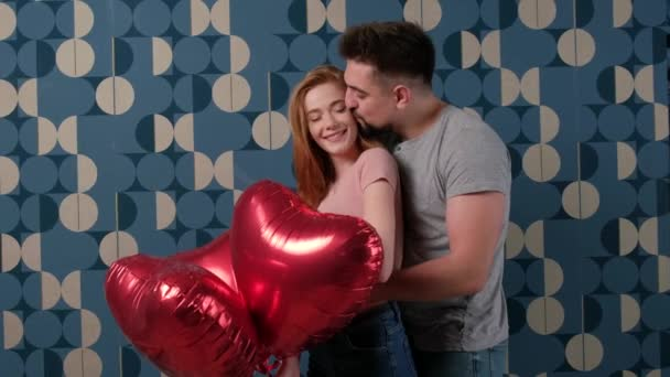 Nice studio shot of a caucasian couple embracing on a blue wall holding red heart shaped air balloons