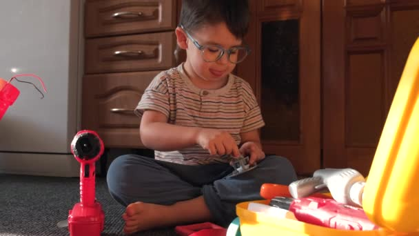 Small caucasian boy with glasses is playing on the floor with plastic toys at home