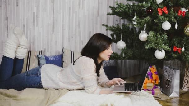 Krásná mladá žena, ležící pod vánoční stromeček a používání notebooku