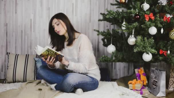 Krásná mladá žena, sedí a čtení knihy pod stromeček
