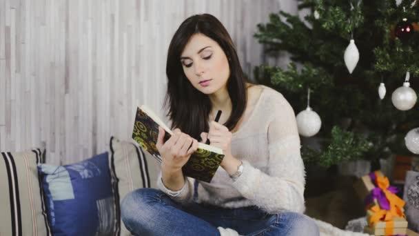Krásná mladá žena, sedící pod vánoční stromeček a seznam dárků