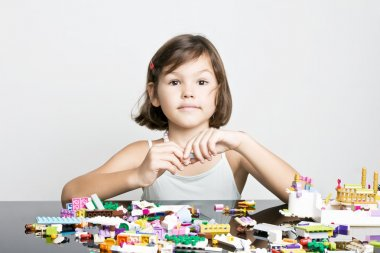 Little girl playing in lego blocks