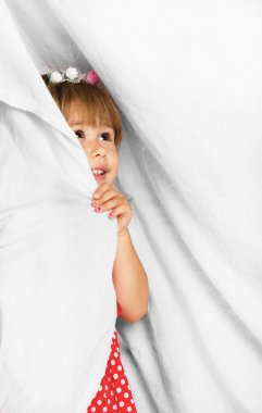 Little girl looking through the curtain