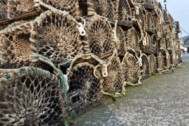Group of old wooden lobster traps stacked on wharf