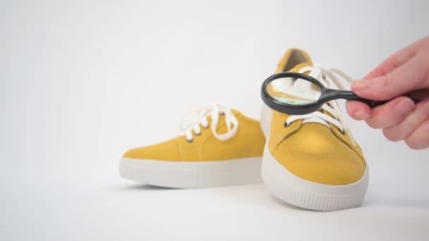 Inspektion eines Schuhs mit einer Lupe. Gelbe Stoffturnschuhe. Hand mit einer Lupe im Rahmen. Gründliche Prüfung der Schuhe