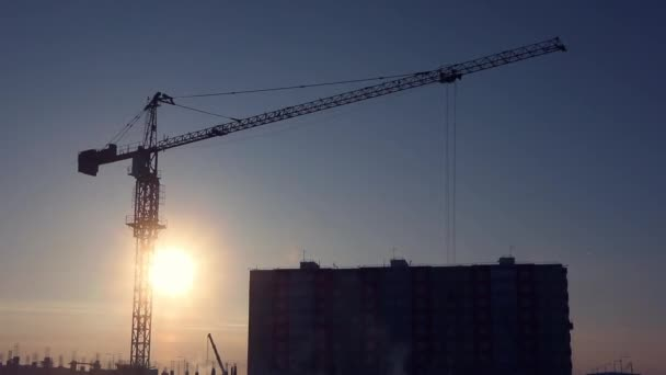 Construction cranes in winter on a cloudyless sky and rising sun background. The concept of building houses, urban development. Copyspace, background image. Cityscape.