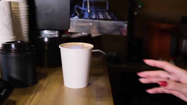 Egy papír kávéscsésze van a pulton egy kávézóban. A csészét egy vörös körmös nő fogja meg. Reggeli ötlet, kávé elvitelre..