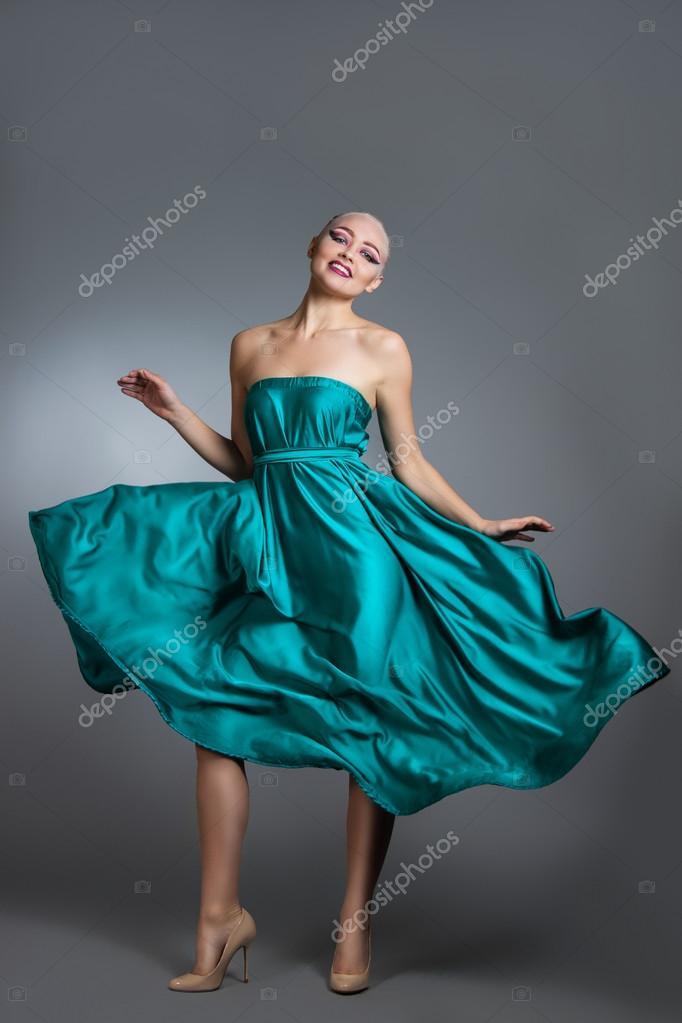 5346a822c68395 Vrouw in zijden jurk zwaaien op wind. Vliegen en fladderende gown doek over  grijze achtergrond
