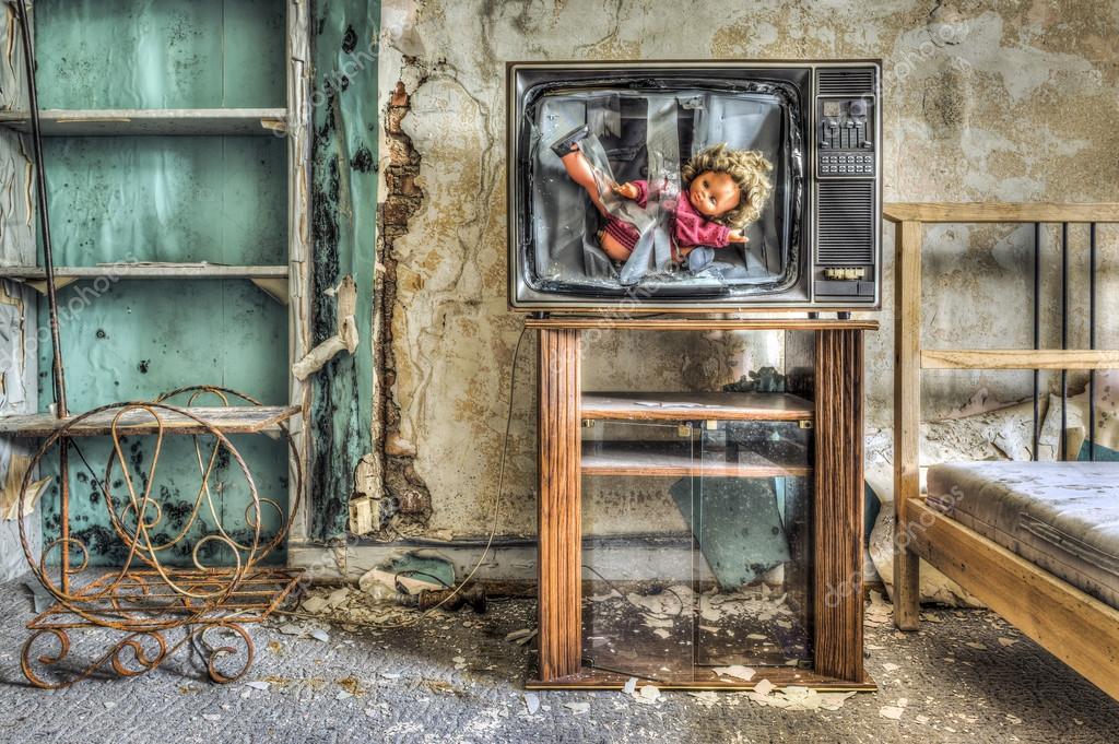 Gebroken Tv met pop in scherm in een bouwvallige slaapkamer ...