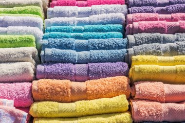 Colorful bath towels stacked on rows in market