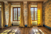 Okna s žluté závěsy v opuštěném hradě
