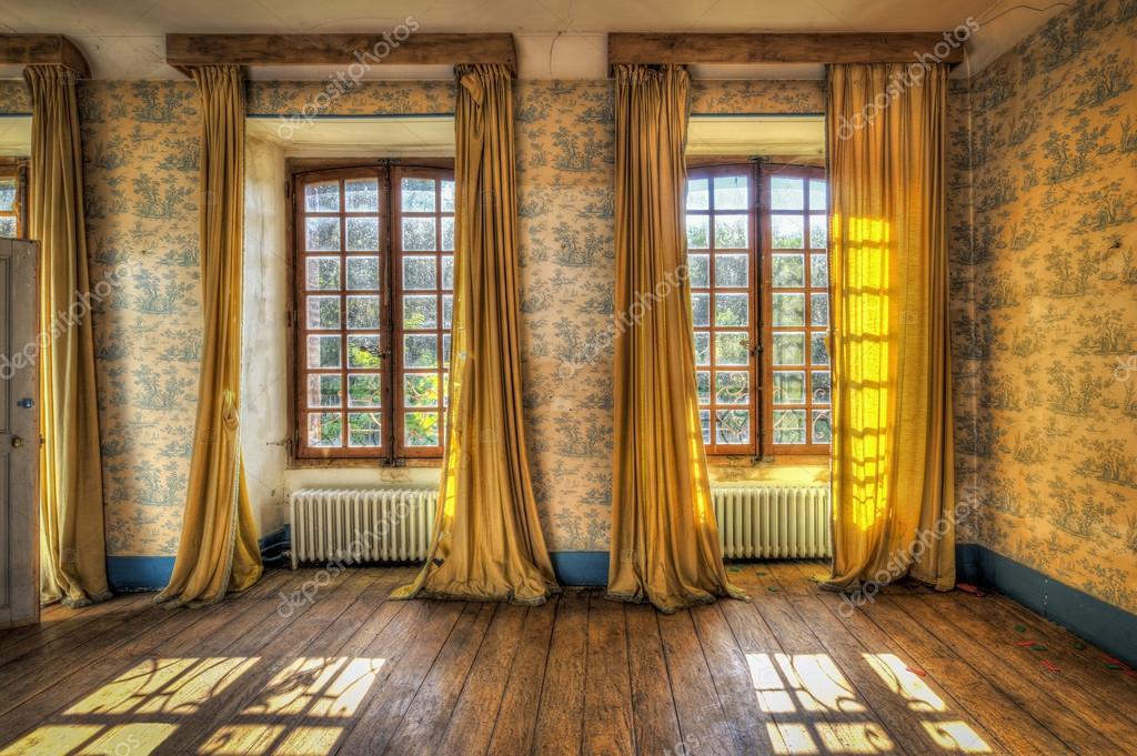 windows met gele gordijnen in een verlaten kasteel stockfoto