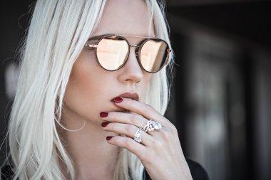 Beautiful blonde girl in sunglassses outdoor