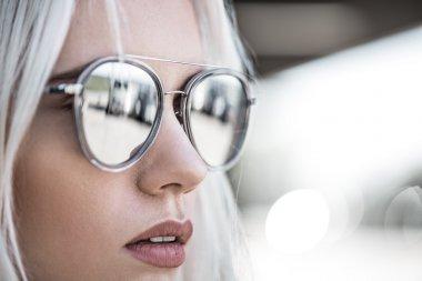 Beautiful blonde girl in grey sunglassses outdoor