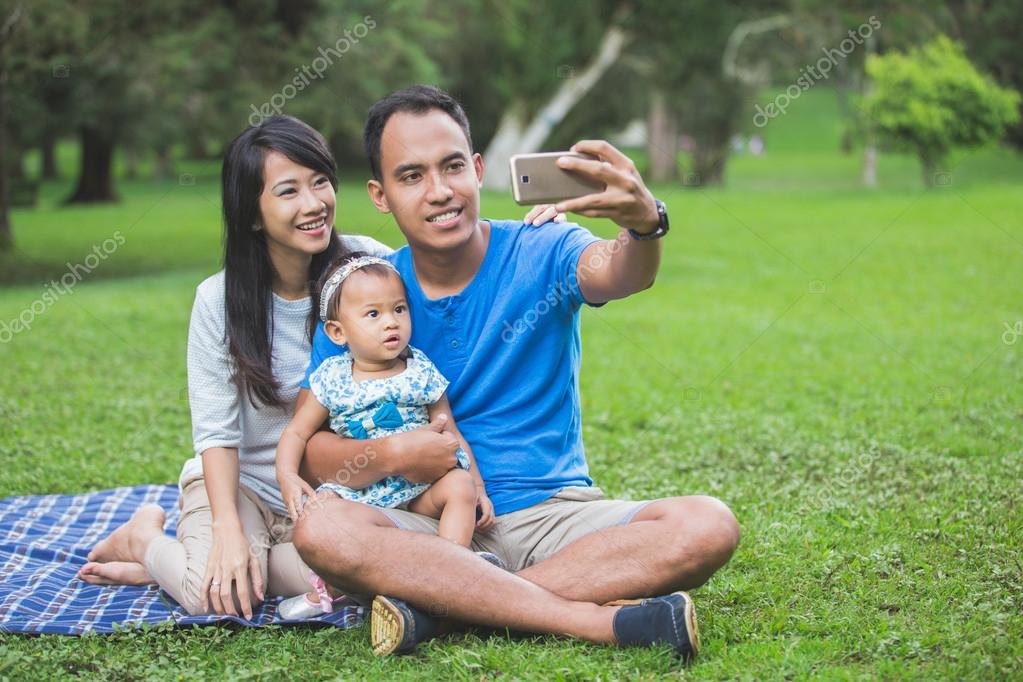 family taking selfie using mobile phone