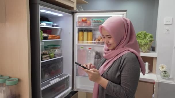 muslim young woman using her smartphone to buy groceries while open her fridge